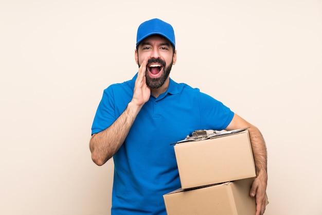 Repartidor con barba sobre pared aislada gritando y anunciando algo