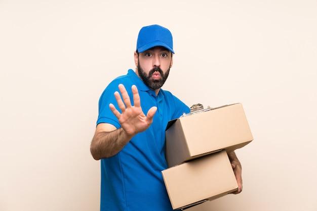 Repartidor con barba sobre pared aislada nervioso estirando las manos al frente