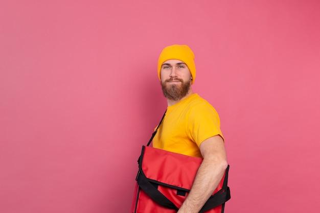 Repartidor barbudo europeo con caja con comida en rosa