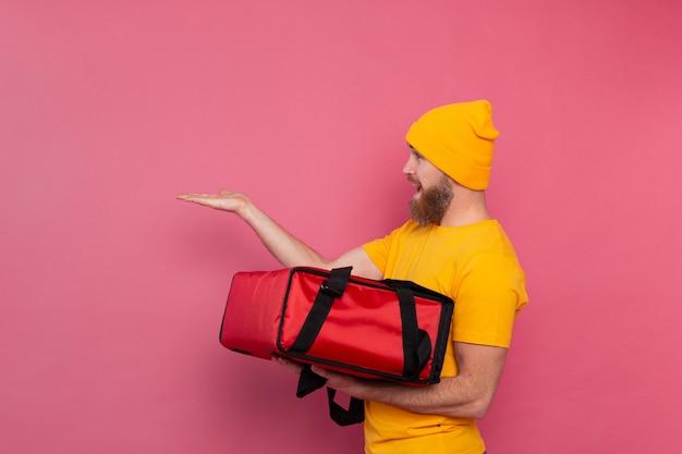 Repartidor barbudo europeo con caja con comida sonriendo y señalando con el dedo a la izquierda en rosa