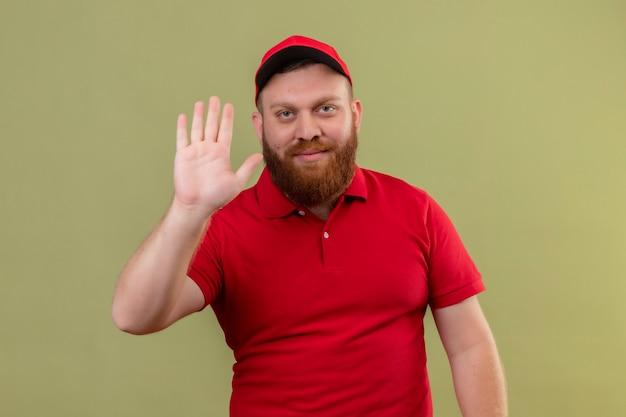 Repartidor barbudo joven en uniforme rojo y gorra sonriendo amable mirando a cámara saludando con la mano