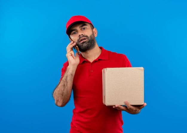 Repartidor barbudo en uniforme rojo y gorra con paquete de caja hablando por teléfono móvil con cara seria de pie sobre la pared azul