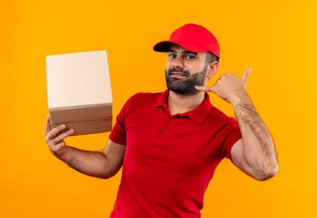 Repartidor barbudo en uniforme rojo y gorra con paquete de caja haciendo gesto de llamarme sonriendo de pie sobre la pared naranja