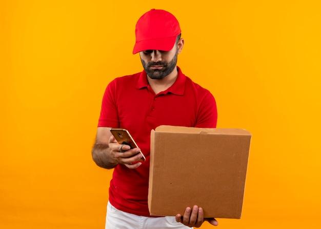 Repartidor barbudo en uniforme rojo y gorra sosteniendo la caja de pizza abierta enviando mensajes de texto en el mensaje del teléfono móvil de pie sobre la pared naranja