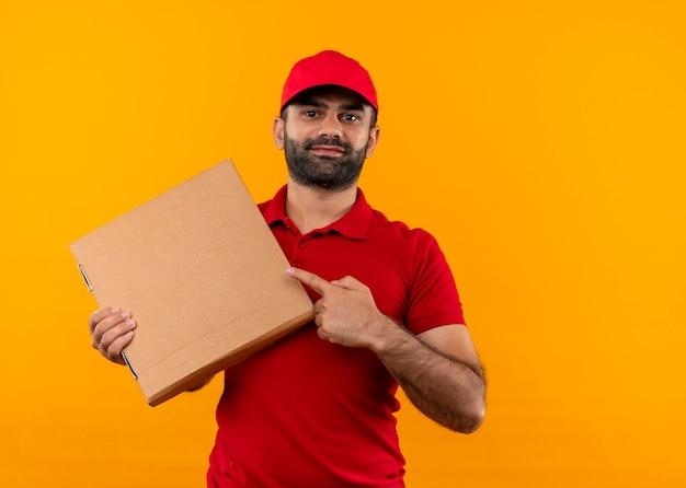 Repartidor barbudo en uniforme rojo y gorra sosteniendo la caja de pizza apuntando con el dedo a ella sonriendo confiado de pie sobre la pared naranja