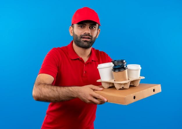 Repartidor barbudo con uniforme rojo y gorra sosteniendo una caja de pizza y tazas de café con aspecto confundido y muy ansioso de pie sobre la pared azul