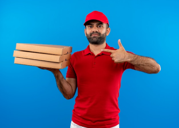Repartidor barbudo en uniforme rojo y gorra sosteniendo una pila de cajas de pizza apuntando con el dedo a las cajas sonriendo de pie sobre la pared azul