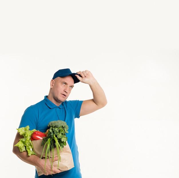 Repartidor con bolsa de supermercado posando mientras indiferente