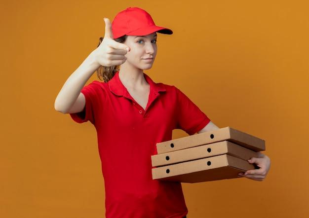 Repartidor bonita joven confiada en uniforme rojo y gorra sosteniendo paquetes de pizza y haciendo gesto de pistola en la cámara aislada sobre fondo naranja