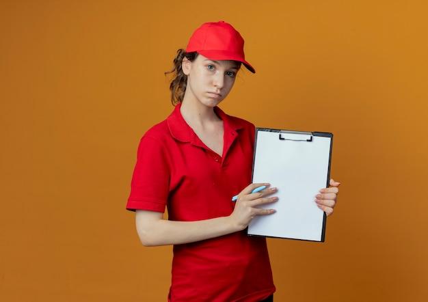 Repartidor bonita joven en uniforme rojo y gorra mirando a la cámara sosteniendo la pluma y mostrando el portapapeles en la cámara aislada sobre fondo naranja con espacio de copia