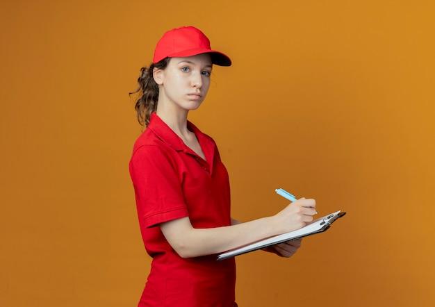 Repartidor bonita joven en uniforme rojo y gorra de pie en vista de perfil sosteniendo bolígrafo y portapapeles preparándose para escribir y mirando a cámara aislada sobre fondo naranja con espacio de copia