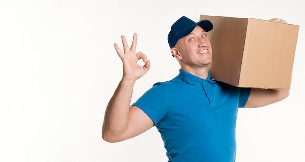 Repartidor con caja de cartón en el hombro y signo bien