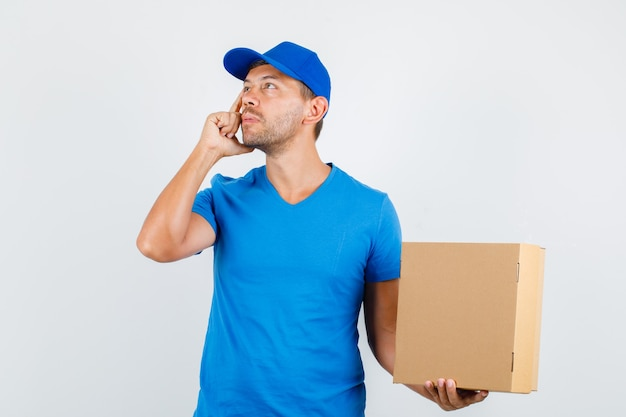 Repartidor con caja de cartón mientras mira hacia arriba en camiseta azul