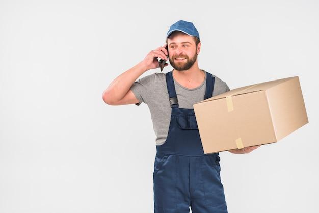 Repartidor con caja grande hablando por teléfono
