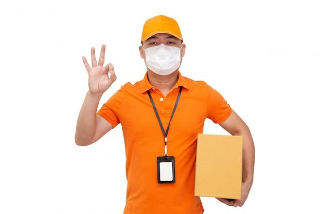 Repartidor con caja de paquetería y máscara protectora para prevenir el virus covid-19 y mostrando bien aislado en la pared blanca, envío de compras en línea y concepto de servicio de entrega rápida