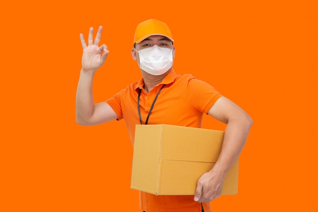 Repartidor con caja de paquetería y con máscara protectora para prevenir el virus covid-19 y mostrando bien aislado en la pared naranja, envío de compras en línea y concepto de servicio de entrega rápida