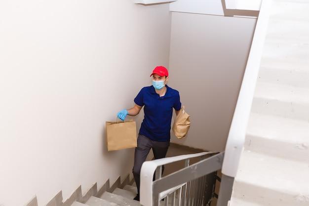 Repartidor con cajas de cartón en guantes de goma y máscara. compras online y entrega urgente