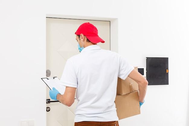 Repartidor con cajas de cartón en guantes de goma médica y máscara. copie el espacio. transporte de entrega rápido y gratuito. compras online y entrega express. cuarentena