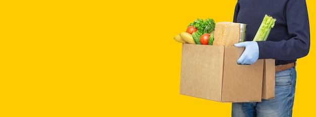 Repartidor con cajas de cartón en guantes de goma médica