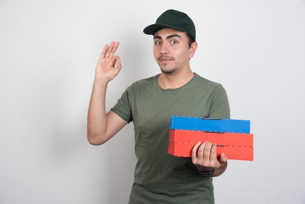 Repartidor con cajas de pizza haciendo bien firmar sobre fondo blanco.
