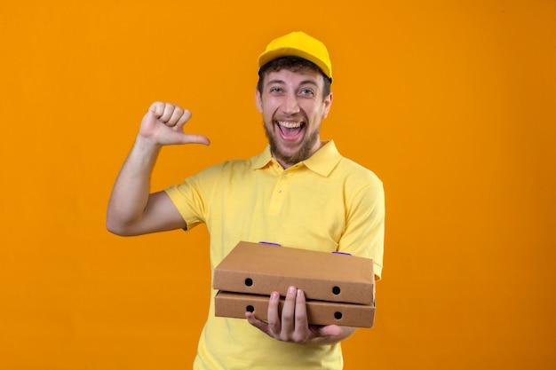 Repartidor en camisa polo amarilla y gorra apuntando a sí mismo mirando confiado autosatisfecho sonriente alegre de pie en naranja aislado