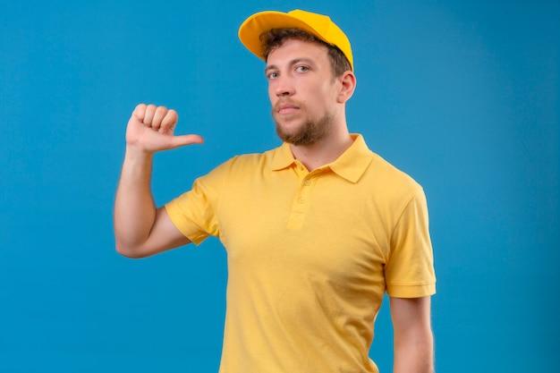 Repartidor en camisa polo amarilla y gorra apuntando a sí mismo mirando seguro de sí mismo satisfecho de pie en azul aislado