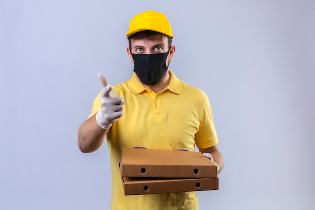 Repartidor con camisa polo amarilla y gorra con máscara protectora negra sosteniendo cajas de pizza apuntando con el dedo índice hacia la expresión de la cámara como pregunta en blanco aislado
