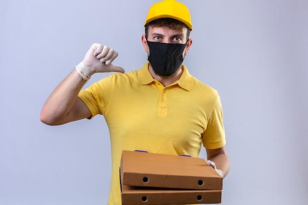 Repartidor con camisa polo amarilla y gorra con máscara protectora negra sosteniendo cajas de pizza apuntando a sí mismo con el pulgar mirando confiado y satisfecho de pie en blanco aislado