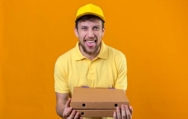 Repartidor en camisa polo amarilla y gorra sosteniendo cajas de pizza divirtiéndose sacando la lengua de pie en naranja