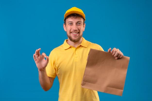 Repartidor en camisa polo amarilla y gorra sosteniendo el paquete de papel sonriendo amable haciendo bien firmar de pie en azul
