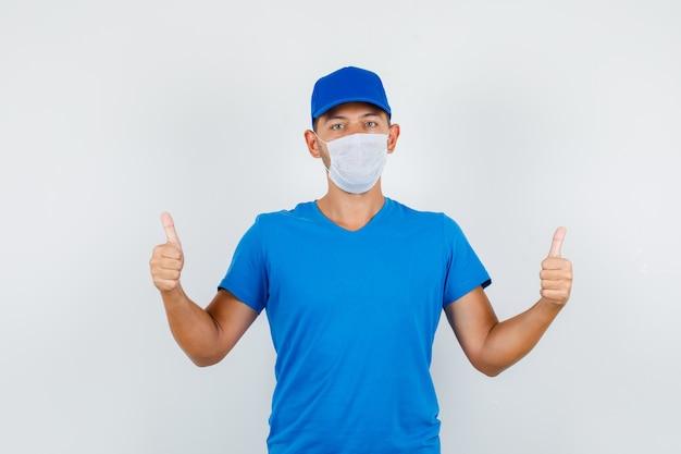 Repartidor en camiseta azul, gorra, máscara mostrando los pulgares para arriba