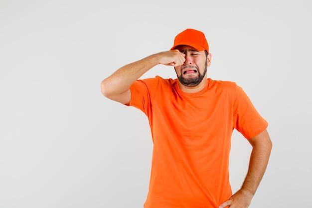 Repartidor en camiseta naranja, gorra frotándose los ojos mientras llora como un niño, vista frontal.