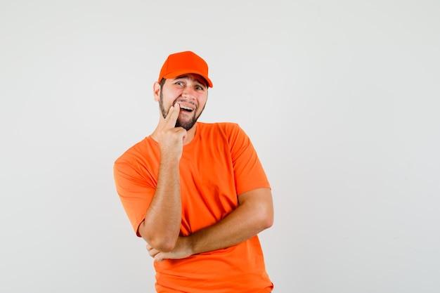 Repartidor en camiseta naranja, gorra que muestra un diente dolorido y que parece incómodo, vista frontal.