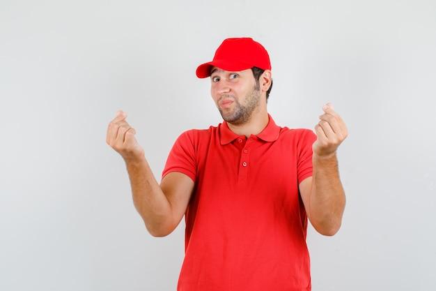 Repartidor en camiseta roja, gorra haciendo signo de amor coreano