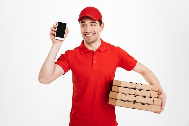 Repartidor en camiseta roja y gorra sosteniendo la pila de cajas de pizza y mostrando la pantalla copyspace del teléfono celular que significa llamada o texto, aislado sobre un espacio en blanco