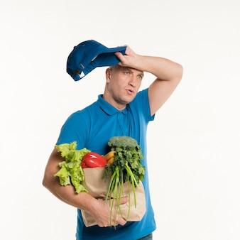 Repartidor cansado posando con bolsa de supermercado