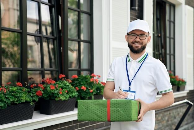 Repartidor con carpeta y caja de regalo