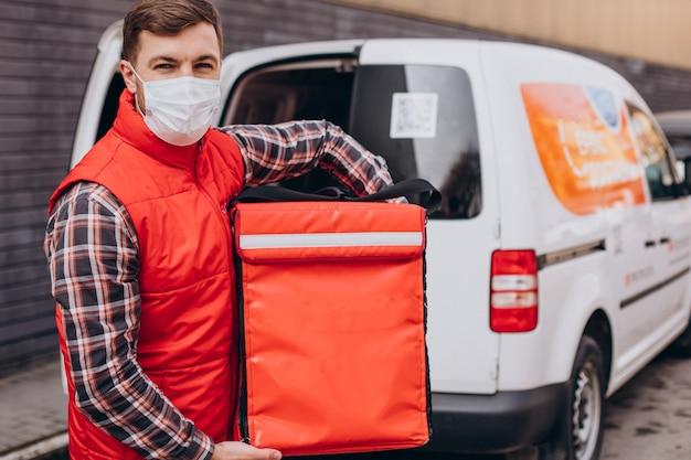 Repartidor de comida poniendo caja de comida en un coche