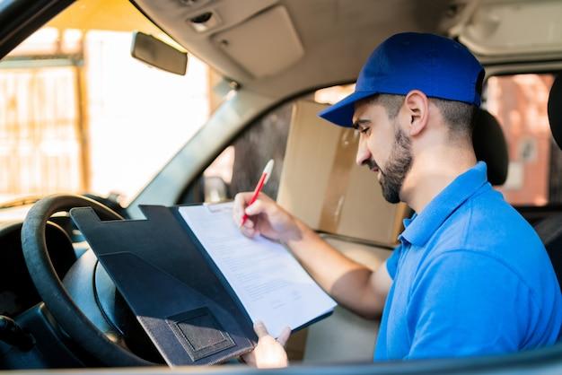 Repartidor comprobando la lista de entrega en furgoneta