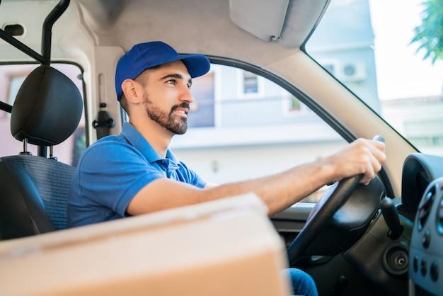 Repartidor conduciendo van con cajas de cartón en el asiento.