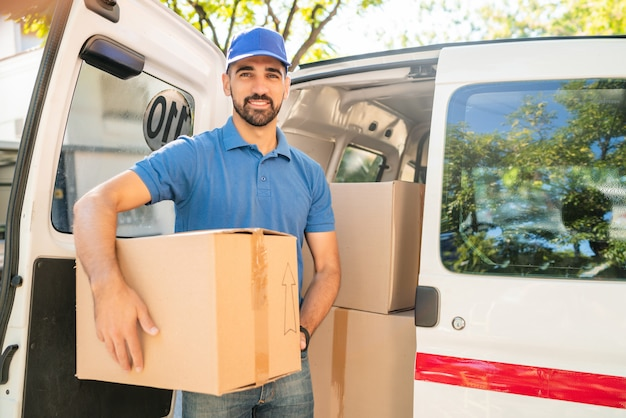 Repartidor descargando cajas de cartón de van.