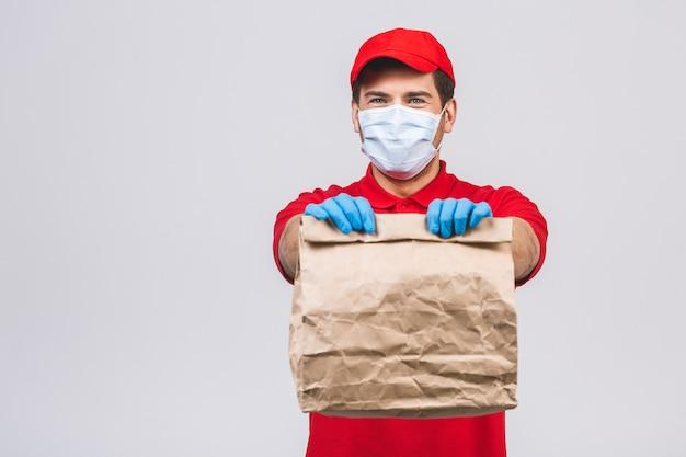 Repartidor empleado en gorra roja camiseta en blanco uniforme mascarilla guantes mantenga caja de cartón vacía aislada en la pared blanca. servicio de cuarentena del virus del coronavirus pandémico 2019-ncov concept.