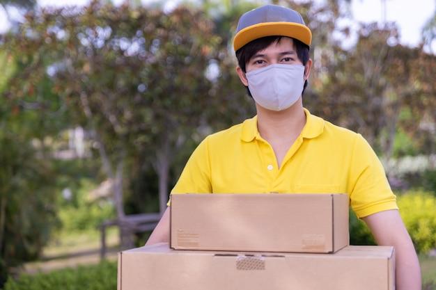 Repartidor empleado con una máscara facial y sosteniendo cajas fuera.