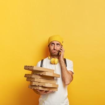 Repartidor enojado con cajas de pizza
