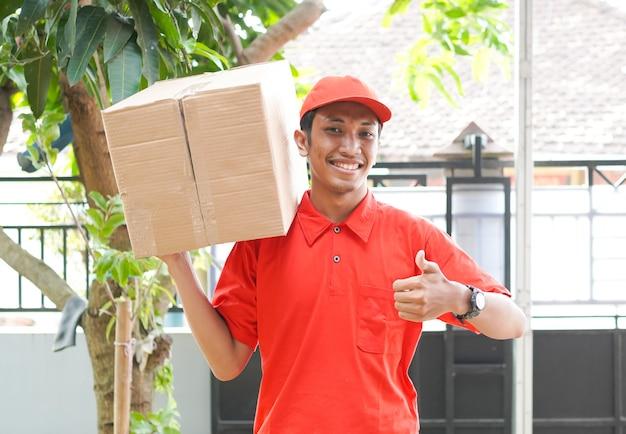 Repartidor entrega la caja al cliente y gesto ok
