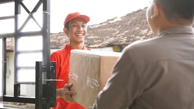 Repartidor entrega la caja al cliente