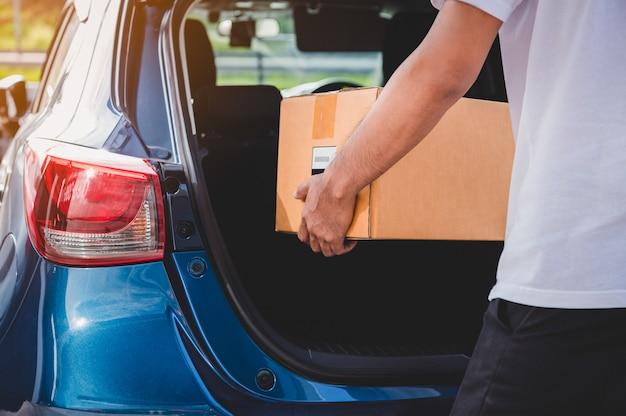 El repartidor entrega una caja de cartón a los clientes a través de la puerta del maletero del automóvil privado
