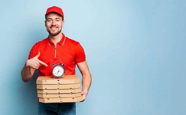 El repartidor es puntual para entregar rápidamente pizzas. fondo cian