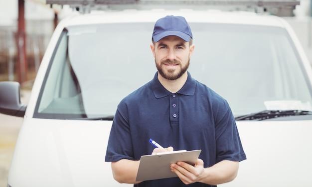 Repartidor escribiendo en el portapapeles delante de su furgoneta