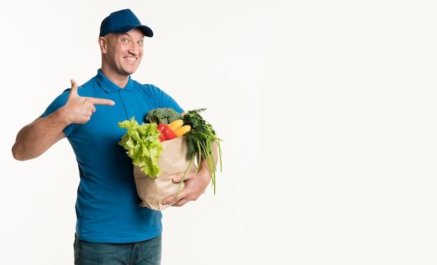 Repartidor feliz apuntando a la bolsa de supermercado en la mano